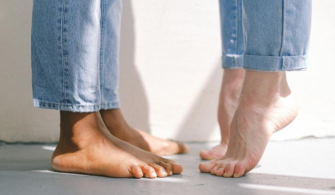 Stopy dwóch osób, jedna z nich stoi na palcach
