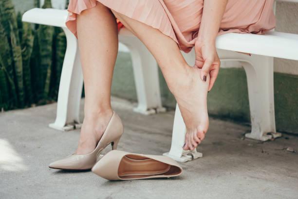 kobieta w szpilkach, rozmasowuje stopy
